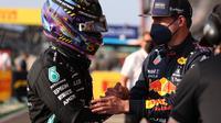 Lewis Hamilton dan Max Verstappen pada sebuah balapan F1 2021. (LARS BARON / AFP)
