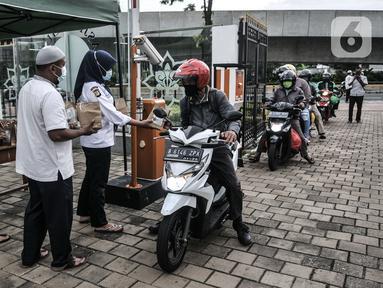 Petugas membagikan takjil kepada pengendara secara drive thru di Kompleks Masjid Al-Azhar, Jakarta, Selasa (13/4/2021). Pengelola Masjid Al-Azhar menyiapkan 500 bungkus takjil per hari yang dibagikan secara drive thru guna mencegah penyebaran COVID-19. (merdeka.com/Iqbal S. Nugroho)