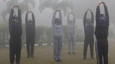 Sejumlah pria melakukan pemanasan saat berolahraga di tengah kabut tebal dan polusi udara di Amritsar, India (2/1). (AFP Photo/Narinder Nanu)
