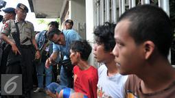 Petugas berbincang dengan warga yang diduga bandar narkoba dan terlibat pengeroyokan di kampung Berlan, Jakarta, Kamis (21/1). Aparat gabungan lakukan penggeledahan dan mencari pelaku tersangka pengeroyokan di kampung Berlan. (Liputan6.com/Yoppy Renato)