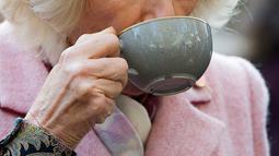 Duchess of Cornwall, Camilla Parker Bowles menikmati teh ketika mengunjungi Swiss Cottage Farmers Market di London utara, Rabu (6/11/2019). Kunjungan Pangeran Charles dan Camila untuk mengucapkan selamat dan memperingati ulang tahun ke-20 pasar tersebut. (Eddie Mulholland / POOL / AFP)