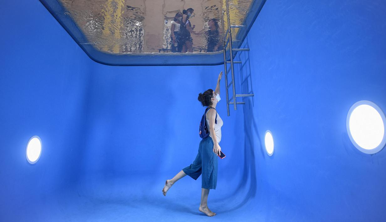 """Seorang perempuan berfoto dengan instalasi """"Kolam Renang"""" karya seniman asal Argentina, Leandro Erlich di Belo Horizonte, Brasil, Senin (20/9/2021). Instalasi tersebut dalam rangka pamerannya yang bertajuk """"A Tension"""". (DOUGLAS MAGNO / AFP)"""