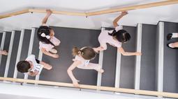 Penari balet cilik berlari menaiki anak tangga mengikuti audisi di Sekolah Ballet Amerika (11/4/2016). Setiap anak berusia 6 sampai 10 tahun diundang untuk mengikuti audisi di Sekolah Balet Amerika. (AFP/Mark Sagliocco)