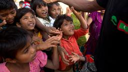 Anak-anak pengungsi Rohingya berdesakan berebut makanan di kamp pengungsi Balukhali, 50 kilometer dari Cox's Bazar, Bangladesh, Rabu (17/1). Sekitar 655.000 orang Rohingya telah melarikan diri ke Bangladesh sejak Agustus 2017. (AP Photo/Manish Swarup)