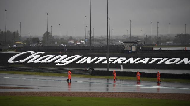 Pekerja menyapu air hujan ke luar lintasan saat sesi latihan dan kualifikasi kualifikasi MotoGP Thailand 2019 di Sirkuit Internasional Buriram, Sabtu (5/10/2019). Pekerja harus bekerja keras untuk mengeluarkan air hujan dari lintasan. (Lillian SUWANRUMPHA/AFP)