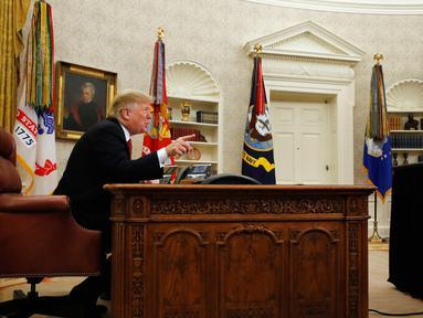 Presiden AS Donald Trump berbicara dengan prajurit militer melalui konferensi video di Gedung Putih, Selasa (25/12). Trump mengucapkan selamat Natal kepada para prajurit. (AP Photo/Jacquelyn Martin)