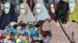 Pengunjung memilih pakaian di Skybridge Pasar Tanah Abang, Jakarta, Rabu (28/4/2021). Jumlah pengunjung dan aktivitas perdagangan kebutuhan pakaian Lebaran di jembatan multiguna ini mulai mengalami peningkatan memasuki 2 minggu menjelang Idul Fitri. (merdeka.com/Iqbal S. Nugroho)