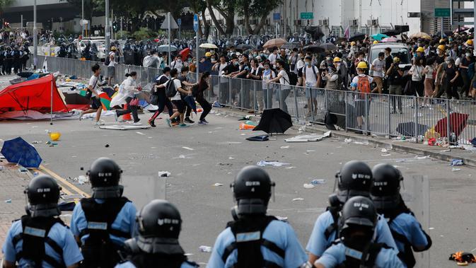 Polusi anti huru hara berusaha membubarkan demonstran di luar gedung Dewan Legislatif, Hong Kong, Rabu (12/6/2019). Bentrok diawali ketika para pengunjuk rasa merangsek melewati garis polisi dan memaksa masuk ke gedung Dewan Legislatif. (AP Photo/Kin Cheung)