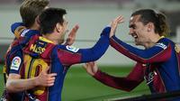 Pemain Barcelona, Lionel Messi (tengah) dan Antoine Griezmann (kanan) merayakan gol kontra Getafe pada lanjutan Liga Spanyol 2020/2021 di Stadion Camp Nou, Jumat (23/4/2021) dini hari WIB. (Lluis Gene/AFP)