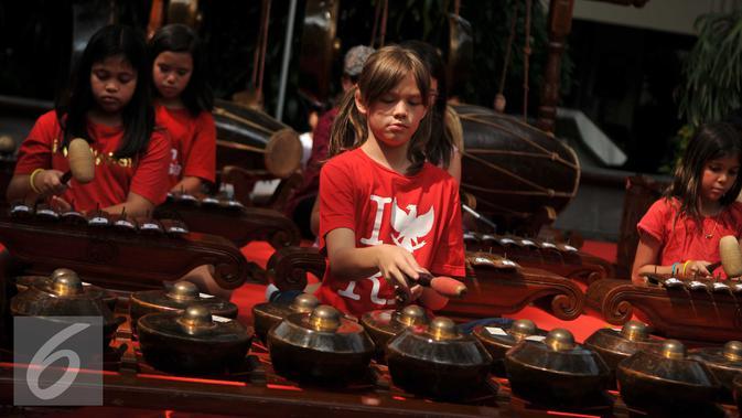 Siswa memainkan gamelan di pelataran Jakarta Intercultural School (JIS) Pattimura, Jakarta, Rabu (24/8). Ratusan siswa diperkenalkan dengan lomba tradisional sekaligus pengenalan budaya Indonesia. (Liputan6.com/Gempur M Surya)