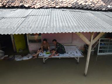 Aktivitas warga terdampak banjir di Desa Sindangsari, Kabupaten Bekasi, Jawa Barat, Rabu (24/2/2021). Sebagian rumah warga masih terendam banjir yang disebabkan jebolnya tanggul Sungai Citarum dan luapan Sungai Ciherang. (merdeka.com/Imam Buhori)