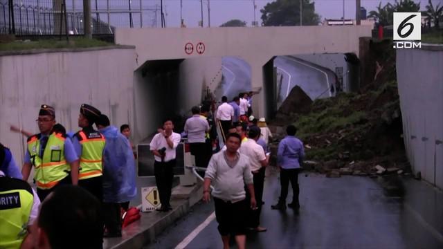 Tebing underpass di jalan perimeter selatan longsor akibat hujan lebat. Sebuah mobil berpenumpang dua orang tertimbun longsoran.