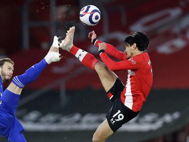 Gelandang Leicester City, James Maddison (kiri) berebut bola dengan gelandang Southampton, Takumi Minamino dalam laga lanjutan Liga Inggris 2020/2021 pekan ke-34 di St Mary's Stadium, Southampton, Jumat (30/4/2021). Leicester bermain imbang 1-1 dengan Southampton. (AFP/Kirsty Wigglesworth/Pool)
