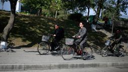 Sejumlah pria Korea Utara mengendarai sepeda mereka di Pyongyang, Korea Utara, (21/10).  (AP Photo / Dita Alangkara)