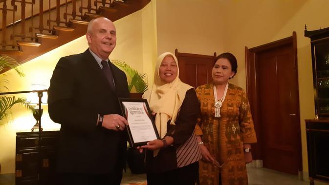 Duta Besar AS untuk RI Joseph Donovan (kiri) memberikan penghargaan kepada Maizidah Salas (tengah) atas prestasinya menerima 2018 TIP Report Heroes. Turut disaksikan oleh Deputi Menteri Kementerian PPPA Vennetia Danes (4/9/2018) (Liputan6.com)