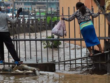 Pejalan kaki berjalan di pagar untuk menyebrang menyusuri jalan yang banjir menuju tempat kerja setelah hujan deras di Nairobi, Kenya (15/3). (AFP Photo/Simon Maina)
