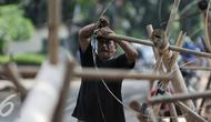 Pedagang mengikat bambu di bagian pohon pinang yang akan digunakan untuk perlombaan 17 Agustus nanti, Jakarta, Selasa (9/8). Jelang HUT RI ke-71, pedagang pohon pinang mulai ramai. (Liputan6.com/Yoppy Renato)