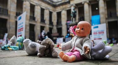 Boneka mainan diletakkan di halaman gedung Kongres Kolombia untuk memprotes kekerasan seksual terhadap anak-anak di Bogota, Selasa (20/11). Protes bertujuan untuk meningkatkan kesadaran tentang tanggung jawab perlindungan anak-anak. (DANIEL MUNOZ/AFP)