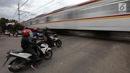 Pengendara sepeda motor menghentikan kendaraannya saat sebuah kereta api melintas di perlintasan kereta api tanpa palang pintu di kawasan Kelingkit, Rawa Buaya, Jakarta Barat, Selasa (26/2). (Liputan6.com/Johan Tallo)