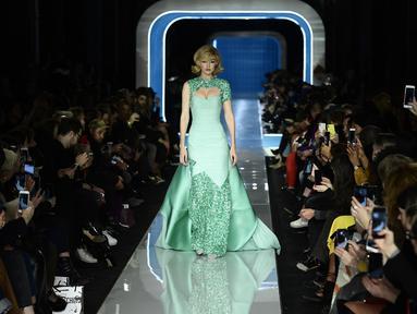 Model AS, Gigi Hadid berjalan membawakan koleksi terbaru Moschino di panggung runway Milan Fashion Week 2018, Rabu (21/2). Gigi terlihat cantik dengan gaun warna hijau muda beraksen sparkling di bagian lengan dan leher serta kakinya. (Miguel MEDINA/AFP)