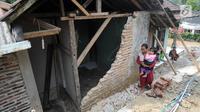 Warga berjalan melewati tembok yang roboh setelah gempa mengguncang Mandalawangi, Pandeglang, Banten, Sabtu (3/8/2019). Getaran akibat gempa Banten terasa ke kota-kota lain di Sumatera bagian selatan hingga Jawa bagian barat. (merdeka.com/Arie Basuki)