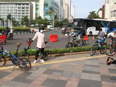 Seorang wanita berpose dengan sepedanya di kawasan Bundaran HI, Jakarta, Minggu (3/01/2021). Sejumlah aktivitas pesepeda melintasi jalan sudirman-thamrin di minggu pertama 2021, meski Car Free Day saat ini belum diberlakukan karena PSBB. (Liputan6.com/Herman Zakharia)