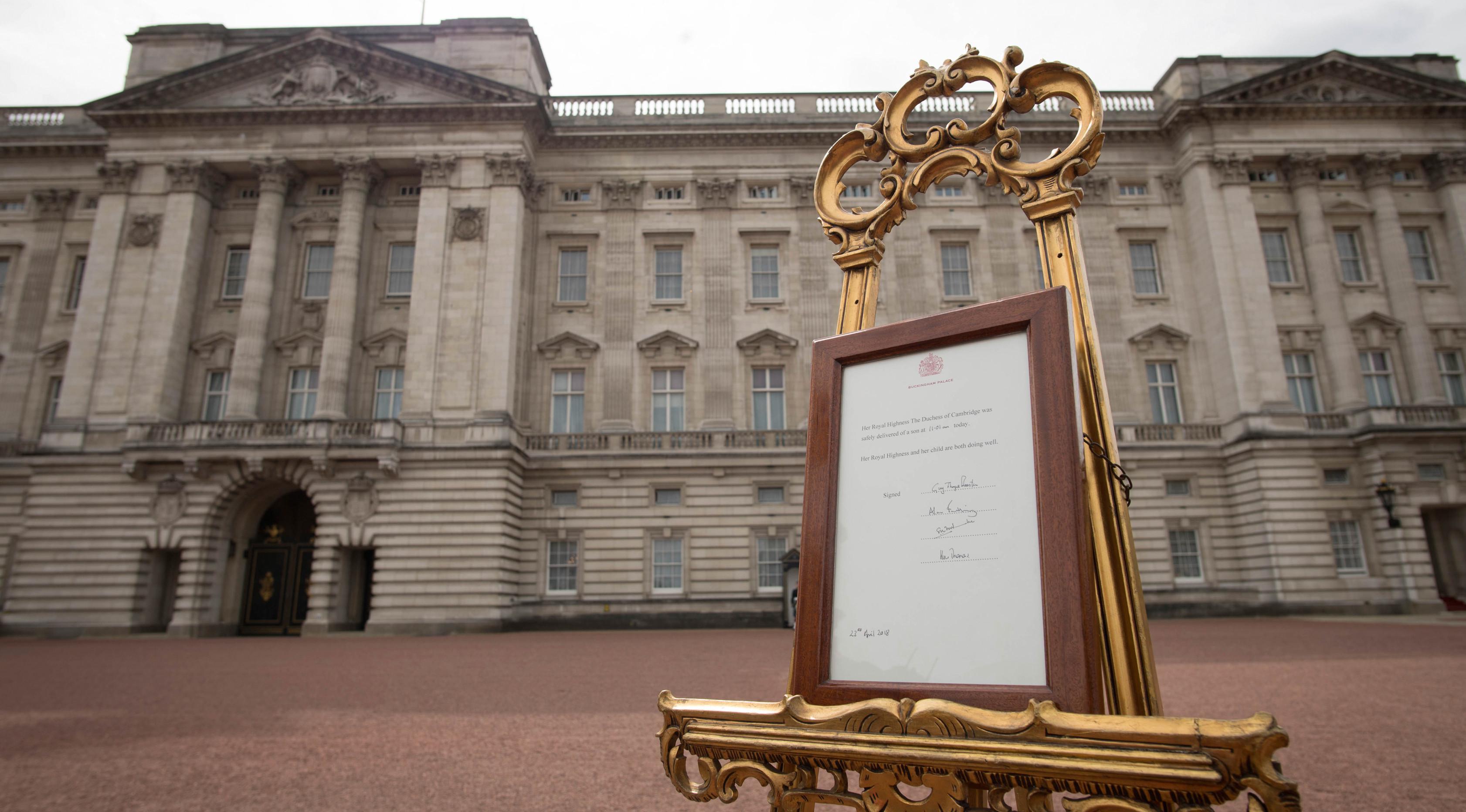 Pengumuman kelahiran bayi baru kerajaan terpajang di halaman depan Istana Buckingham, London, Inggris, Senin (23/4). Kate Middleton tampil di depan umum tujuh jam usai melahirkan. (Pool Photo via AP)
