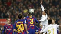 Bek Barcelona, Gerard Pique, duel udara dengan bek Real Madrid, Raphael Varane, pada laga La Liga 2019 di Stadion Camp Nou, Rabu (18/12). Kedua tim bermain imbang 0-0. (AP/Bernat Armangue)