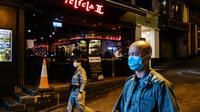 Aparat kepolisian dikerahkan untuk berpatroli di kawasan hiburan malam Lan Kwai Fong, Hong Kong, (5/5/2020). Pemimpin Hong Kong, Carrie Lam memerintahkan penutupan sementara terhadap semua bar dan pub sebagai upaya menghentikan penyebaran virus corona Covid-19. (AFP/May James)