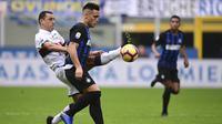 Striker Inter Milan, Lautaro Martinez, berebut bola dengan gelandang Genoa, Romulo, pada laga Serie A Italia di Stadion San Siro, Milan, Sabtu (3/11). Inter menang 5-0 atas Cagliari. (AFP/Miguel Medina)