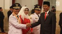 Presiden Joko Widodo atau Jokowi (kanan) menyalami Gubernur Riau Syamsuar saat pelantikan di Istana Negara, Jakarta, Rabu (20/2). Syamsuar dilantik menjadi Gubernur Riau periode 2019-2024. (Liputan6.com/Angga Yuniar)