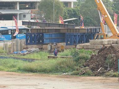 Pekerja beraktivitas di sekitar proyek Depok Metro Stater di Depok, Jawa Barat, Senin (17/6/2019). Proyek ini nantinya akan berbasis Transit Oriented Development (TOD) yang mensinergikan hubungan antarmoda dengan berbagai tipe transportasi. (Liputan6.com/Immanuel Antonius)