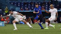 Penyerang Italia, Domenico Berardi menembak bola dari kawalan bek Swiss, Ricardo Rodriguez dan Manuel Akanji selama pertandingan grup A Euro di stadion Olimpiade di Roma, Rabu (16/6/2021). Dengan hasil ini, Italia kokoh dipuncak klasemen dengan poin enam. (Andreas Solaro/Pool Photo via AP)