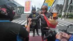 """Warga mengenakan kostum superhero Gundala dan Batman menawarkan minuman herbal tradisional Indonesia """"Jamu"""" kepada pengendara saat aksi sosialisasi pencegahan virus corona di Solo (4/3/2020). Jamu dapat meningkatkan daya tahan tubuh agar terhindar dari berbagai penyakit. (AFP Photo/Anwar Mustafa)"""
