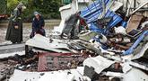 Para pekerja memeriksa puing-puing setelah gempa bumi di daerah Luxian di provinsi Sichuan China barat daya, Kamis (16/9/2021). Gempa bumi meruntuhkan rumah, menewaskan tiga orang dan melukai belasan lainnya. (Chinatopix Via AP)
