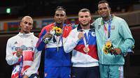 (Kiri ke kanan) Peraih medali perak Benjamin Whittaker, peraih medali emas Arlen Lopez dari Kuba, peraih medali perunggu Imam Khataev dari Rusia dan Loren Berto Alfonso Dominguez dari Azerbaijan di podium usai pertarungan final tinju kelas ringan di Olimpiade Tokyo 2020. (Buda MENDES / POOL / AFP)