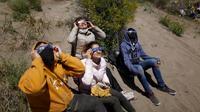 Orang-orang menyaksikan gerhana matahari total di Piedra del Aguila, Argentina, Senin (14/12/2020). Gerhana matahari total terlihat dari wilayah Patagonia utara Argentina dan dari Araucania di Chili. (AP Photo/Natacha Pisarenko)