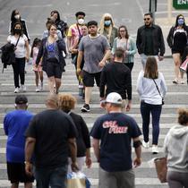 Pejalan kaki dengan masker dan tanpa masker berjalan di sepanjang Las Vegas Strip, di Las Vegas Selasa (27/4/2021). Warga Amerika Serikat (AS) yang telah menerima vaksin COVID-19 tidak lagi diwajibkan mengenakan masker saat berada di luar ruangan jika tidak ada kerumuman. (AP Photo/John Locher)