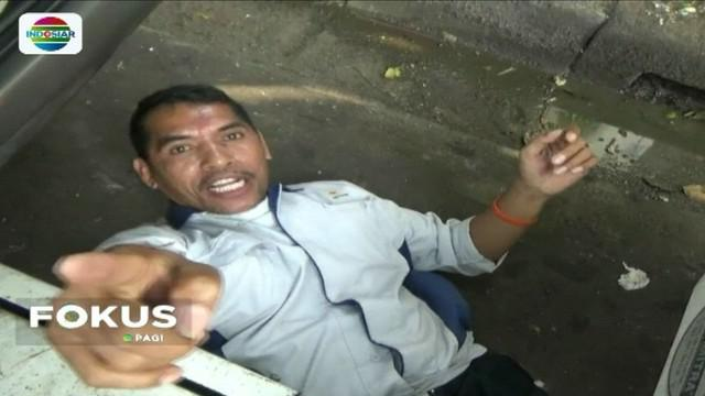 Merasa tidak parkir sembarangan, pria ini nekat berbaring di kolong mobilnya saat kendaraan miliknya tersebut akan diderek oleh petugas.