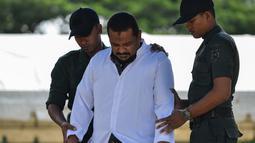 Polisi syariah menggiring manajer hotel, Firman Syahaputra (34) saat akan dihukum cambuk karena mesum di Banda Aceh, Senin (29/10). Firman mendapat hukum cambuk sebanyak 28 kali. (Chaideer Mahyuddin/AFP)