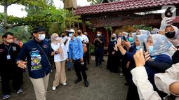 Menteri Pariwisata dan Ekonomi Kreatif Sandiaga Uno (kiri) menyapa warga pada kunjungannya di Desa Wisata Saung Ciburial, Kecamatan Samarang, Garut, Jawa Barat, Senin (18/10/2021). Hujan deras tidak menyurutkan warga untuk menyambut kunjungan kerja Sandiaga Uno. (Liputan6.com/HO/Parekraf)