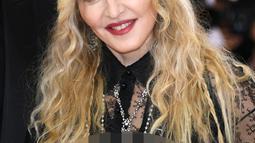 Senyum Madonna saat berpose menghadiri ajang Met Gala 2016 di Metropolitan Museum of Art, New York, Senin (2/5). Madonna hadir bersama desainer Riccardo Tisci dengan busana yang nyentrik dan transparan. (AFP/Larry Busacca)