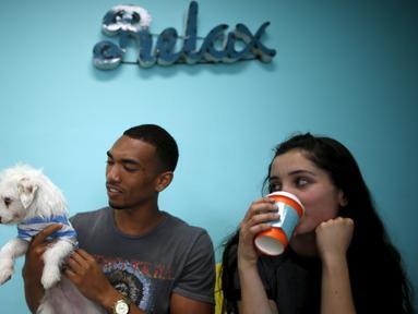 Pengunjung bermain bersama anak anjing saat mengunjungi Dog Cafe di Los Angeles, AS (7/4). Di kafe ini pengunjung dapat bermain dan mengadopsi anjing yang berada di kafe ini. (REUTERS/Lucy Nicholson)