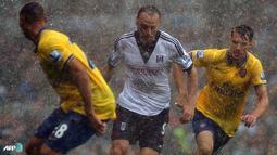 Dimitar Berbatov manghadapi hadangan bek Arsenal di bawah guyuran hujan pada pertandingan Liga Inggris antara Fulham melawan Arsenal di Stadion Craven Cottage, London Sabtu 24 Agustus 2013. (AFP/Carl Court)