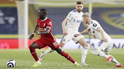 Striker Liverpool,  Sadio Mane, berusaha melewati pemain Leeds United, Ezgjan Alioski, pada laga Liga Inggris di Stadion Elland Road, Senin (19/4/2021). Kedua tim bermain imbang 1-1. (Clive Brunskill/Pool via AP)