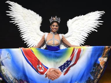 Miss Singapura, Zahra Khanum menampilkan kostum nasionalnya dalam ajang Miss Universe 2018 di provinsi Chonburi, Thailand, Senin (10/12). Khanum mengenakan gaun bergambar pertemuan antara Donald Trump dan Kim Jong-un (Lillian SUWANRUMPHA/AFP)