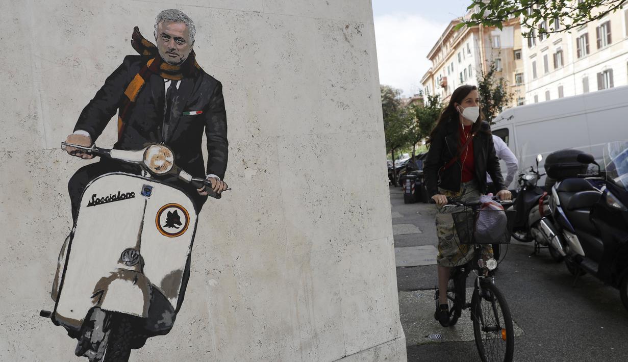 Seorang wanita mengendarai sepedanya di dekat mural Jose Mourinho mengendarai skuter Vespa mengenakan syal merah dan kuning berhias lambang AS Roma di lingkungan Testaccio, Roma (7/5/2021). Mourinho resmi menjabat sebagai pelatih AS Roma untuk musim depan. (AP Photo/Gregorio Borgia)