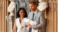 Pangeran Harry dan Meghan Markle berjalan membawa bayi laki-lakinya yang baru lahir di St George's Hall di Windsor Castle di Windsor, London (8/5/2019). Pangeran Harry menyatakan bahwa dia dan Meghan Markle masih memikirkan nama anak mereka. (AFP Photo/Dominic Lipinski)