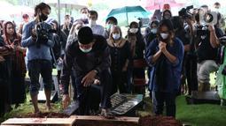 Istri mantan penggawa Timnas Indonesia Ricky Yacobi, Harly Ramayani (kanan) menyaksikan proses pemakaman suaminya di TPU Tanah Kusir, Jakarta, Sabtu (21/11/2020). Ricky Yacobi meninggal dunia pada Sabtu (21/11) akibat serangan jantung pada usia 57 tahun. (Liputan6.com/Helmi Fithriansyah)