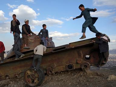 Anak-anak Afghanistan bermain di sisa-sisa tank Soviet di puncak bukit di pinggiran Kabul, Afghanistan (4/3). Mereka sering menghabiskan waktunya dengan bermain di sebuah tank yang sudah hancur dan hasil sitaan para pejuang. (AP Photo/Rahmat Gul)